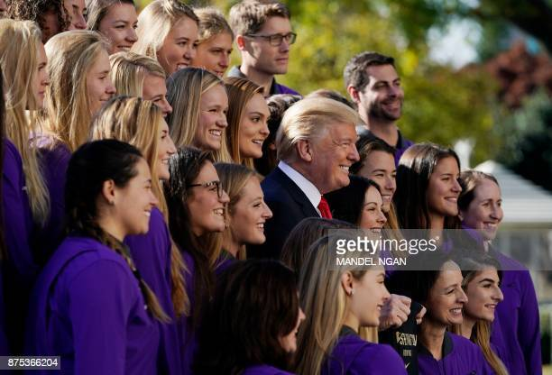 President Donald Trump poses with members of the University of Washington women's rowing team on the South Lawn of the White House during an event...