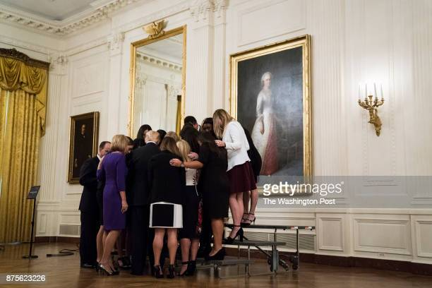 President Donald Trump prays with the University of Oklahoma softball team during an event with NCAA championship teams at the White House in...