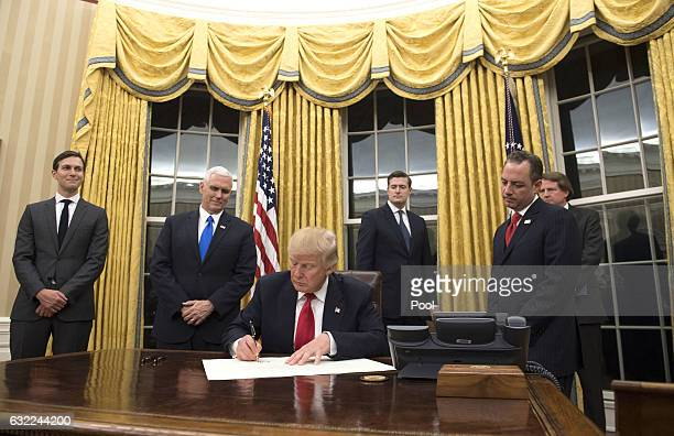 President Donald Trump prepares to sign a confirmation for Homeland Security Secretary James Kelly in the Oval Office at the White House in...