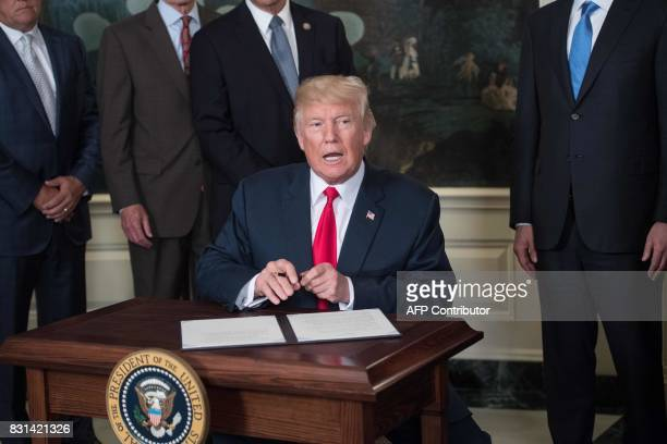 US President Donald Trump prepares to sign a memorandum on addressing Chinas laws policies practices and actions related to intellectual property...