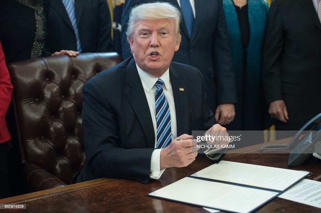 US President Donald Trump prepares to sign an executive order entitled Comprehensive Plan for Reorganizing the Executive Branch in the Oval Office at the White House in Washington, DC, on March 13, 2017. /