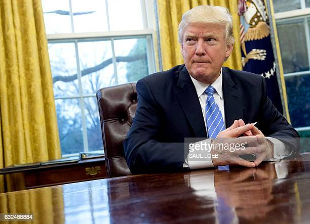 US President Donald Trump prepares to sign several executive orders in the Oval Office of the White House in Washington DC January 23 2017 Trump on...