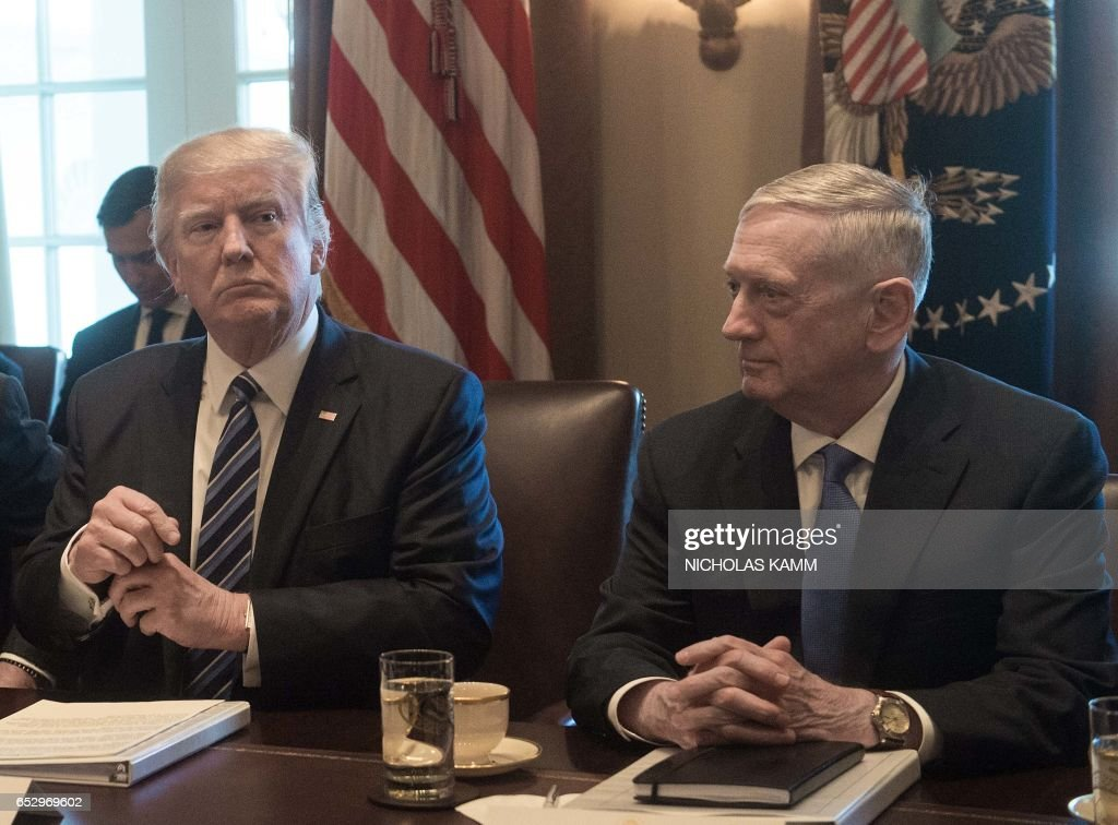 US President Donald Trump prepares to speak to the press before he meets with his cabinet in the Cabinet Room at the White House in Washington, DC, on March 13, 2017, as Defense Secretary James Mattis looks on. /