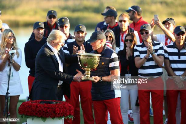 S President Donald Trump presents Captain Steve Stricker and the US Team with the trophy after they defeated the International Team 19 to 11 in the...