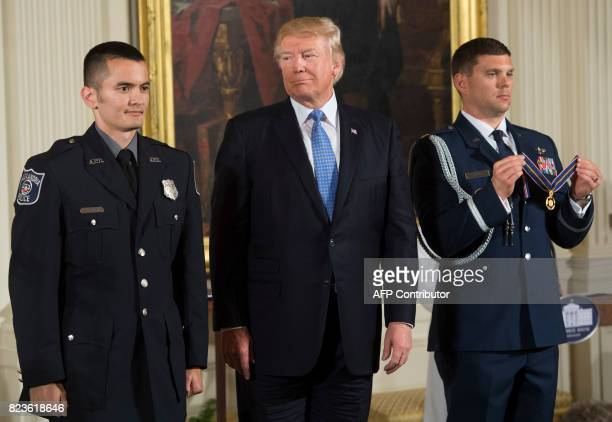 US President Donald Trump presents the Medal of Valor to Alexandria Virginia Police Department Officer Alexander Jensen during a ceremony honoring...