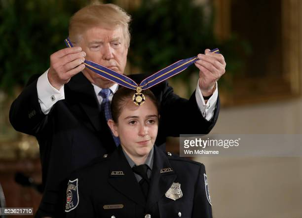 S President Donald Trump presents the Medal of Valor to Alexandria Police officer Nicole Battaglia during an event in the East Room of the White...