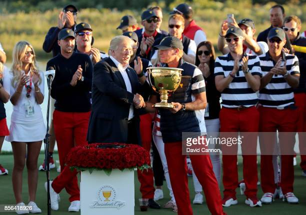 President Donald Trump presents the victorious United States team Captain Steve Stricker with the Presidents Cup after the US won by 1911 during the...