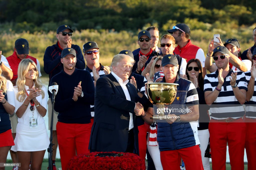 US President Donald Trump presents the victorious United States team Captain Steve Stricker with the Presidents Cup after the US won by 19-11 during the final day singles matches matches in the 2017 Presidents Cup at the Liberty National Golf Club on October 1, 2017 in Jersey City, New Jersey.