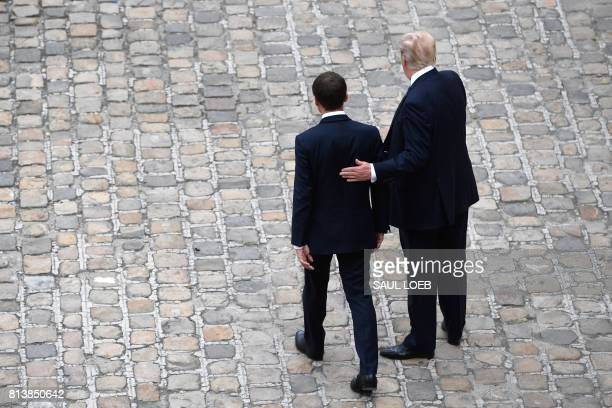 US President Donald Trump puts his hand on the back of French President Emmanuel Macron during a welcome ceremony at Les Invalides in Paris on July...