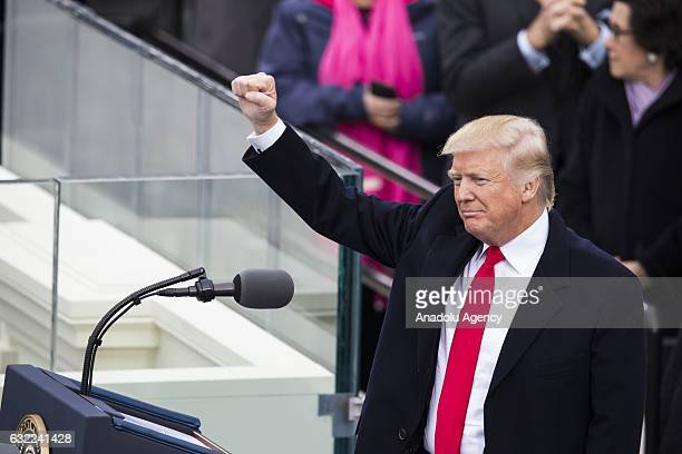 President Donald Trump raises his fist to the crowds during the 58th US Presidential Inauguration after he was sworn in as the 45th President of the...