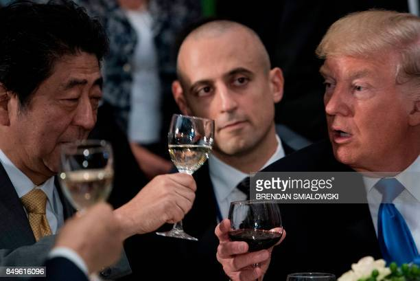 US President Donald Trump raises his glass to a toast by UN SecretaryGeneral Antonio Guterres with Japan's Prime Minister Shinzo Abe and others...