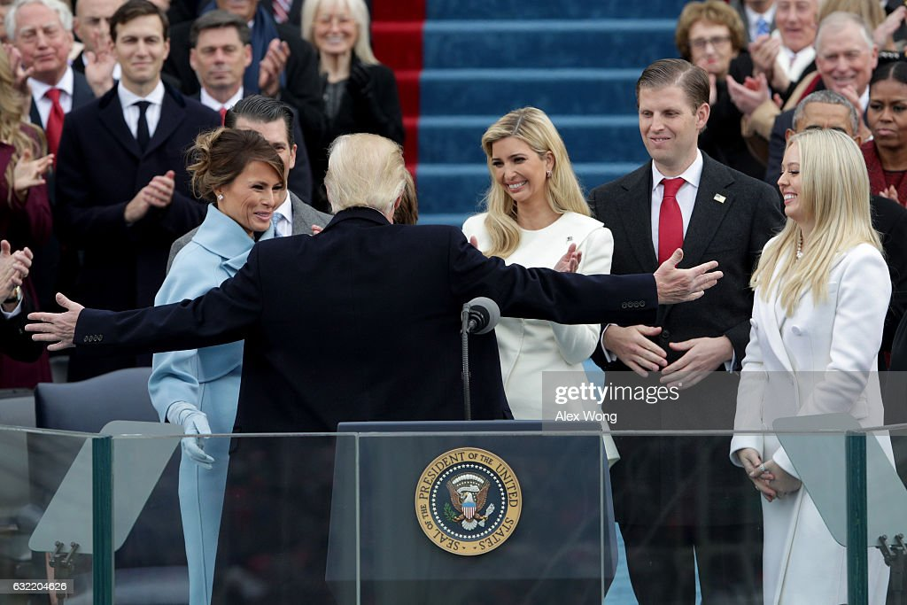 President Donald Trump reaches out to embrace son Barron Trump as First Lady Melania Trump Ivanka Trump Eric Trump and Tiffany Trump look on after...