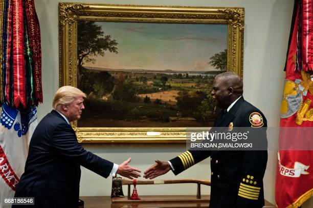 US President Donald Trump reaches to shake Atlanta Fire Chief Joel Baker after being presented with a fire ax before a meeting with first responders...