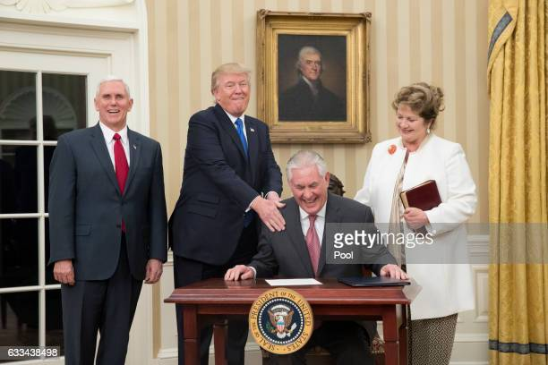 US President Donald Trump reacts after Rex Tillerson accompanied by wife Renda St Clair signed an appointment affidavit after being sworn in as the...
