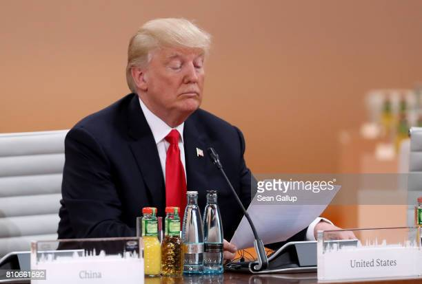 S President Donald Trump reads a document prior to the morning working session on the second day of the G20 economic summit on July 8 2017 in Hamburg...