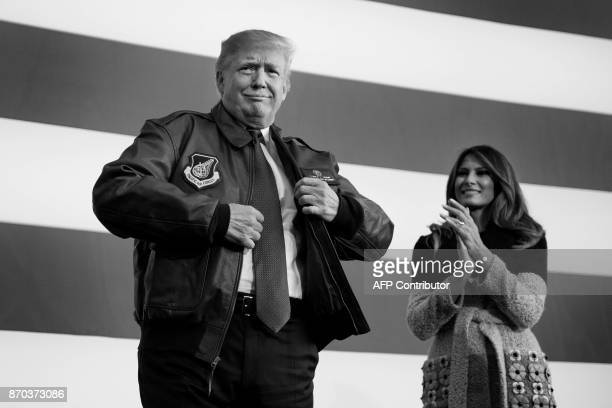 US President Donald Trump receives a bomber jacket from the US Pacific Air Forces as First Lady Melania Trump looks on during an event to speak with...