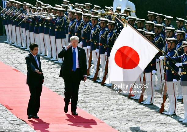 US President Donald Trump reviews the honour guard with Japanese Prime Minister Shinzo Abe during the welcome ceremony at the Akasaka State Guest...