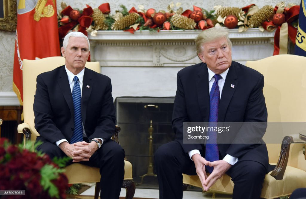 U.S. President Donald Trump, right, and U.S. Vice President Mike Pence, listen during a meeting with congressional leadership in the Oval Office of the White House in Washington, D.C., U.S., on Thursday, Dec. 7, 2017. Trump is meeting with the congressional leaders from both parties to negotiate on a long-term budget deal as Congress prepares to pass a stopgap spending measure to avoid a U.S. government shutdown Saturday. Photographer: Olivier Douliery/Pool via Bloomberg