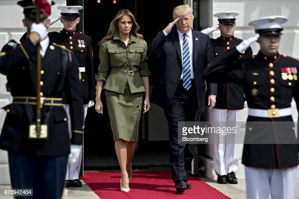 US President Donald Trump right salutes as he walks out of the South Portico of the White House with US First Lady Melania Trump to greet Mauricio...