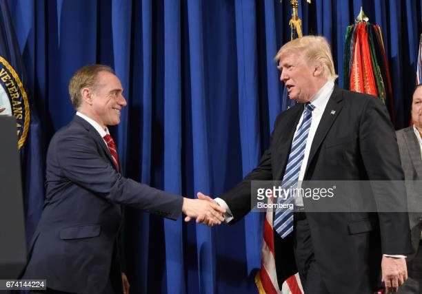 US President Donald Trump right shakes hands with David Shulkin secretary of US Veteran Affairs before speaking and signing an executive order on...