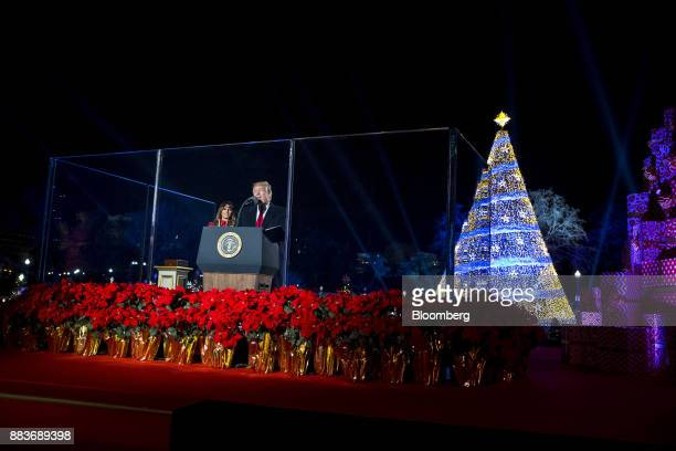 US President Donald Trump right speaks as US First Lady Melania Trump listens during the 95th Annual National Christmas Tree Lighting in Washington...