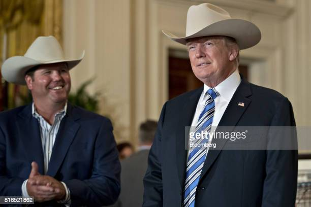 US President Donald Trump right wears a Stetson cowboy hat while participating in a Made in America event with companies from 50 states featuring...