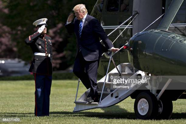US President Donald Trump salutes as exits Marine One on the South Lawn of the White House in Washington DC US on Wednesday May 17 2017 Republican...