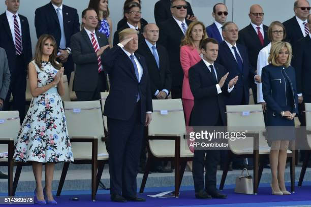 US President Donald Trump salutes as French President Emmanuel Macron his wife Brigitte Macron and US First Lady Melania Trump watch the annual...