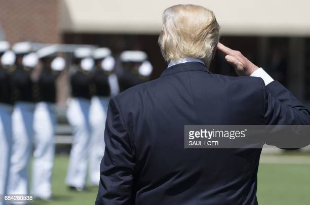 US President Donald Trump salutes as he leaves the US Coast Guard Academy Commencement Ceremony in New London Connecticut May 17 2017 / AFP PHOTO /...