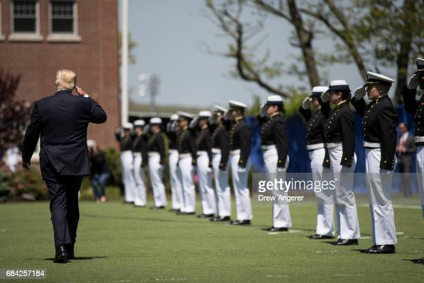 President Donald Trump salutes members of the US Coast Guard as he exits the commencement ceremony for the US Coast Guard Academy May 17 2017 in New...