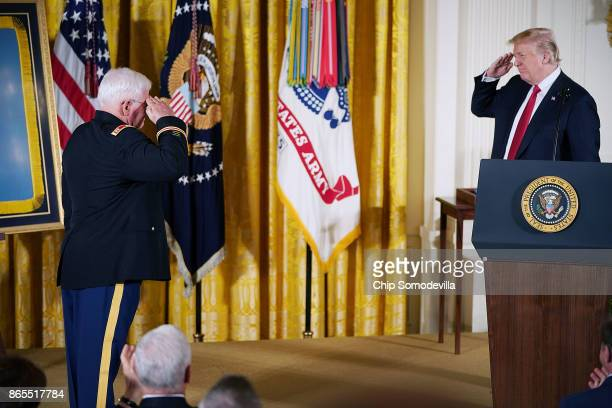 S President Donald Trump salutes retired US Army Capt Gary Rose during his Medal of Honor ceremony in the East Room of the White House October 23...