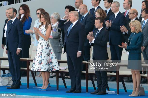 US President Donald Trump salutes US troops flanked by French Prime Minister Edouard Philippe US First Lady Melania Trump French President Emmanuel...