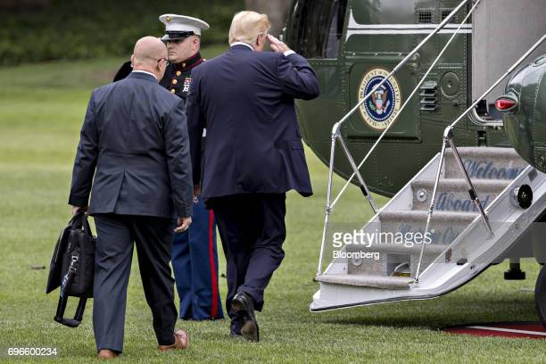US President Donald Trump salutes while boarding Marine One with HR McMaster national security advisor left on the South Lawn of the White House in...