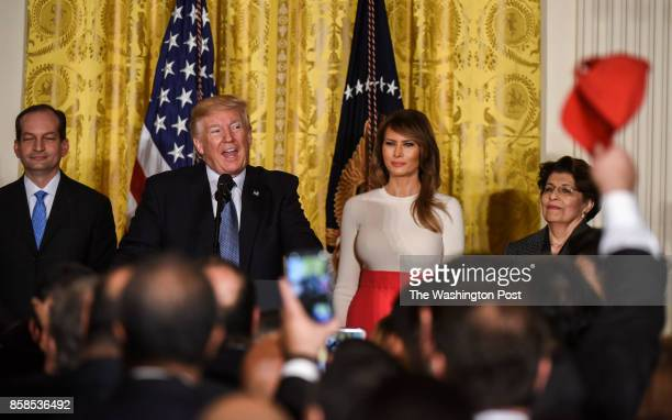President Donald Trump second left hosts a Hispanic Heritage Month event in the East Room as a supporter waves a red cap with 'Build the Wall'...