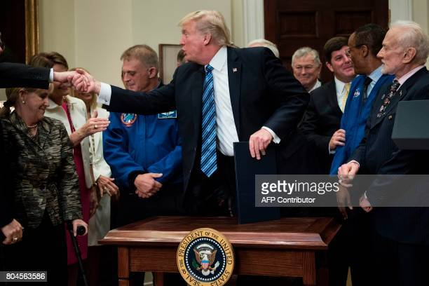 US President Donald Trump shakes hands after signing an executive order about space exploration in the Roosevelt Room at the White House June 30 2017...