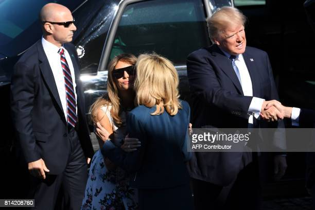 US President Donald Trump shakes hands as he steps out of the US presidential state car called 'The Beast' as US First Lady Melania Trump kisses...