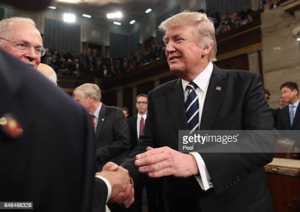 US President Donald Trump shakes hands on his way out after delivering his first address to a joint session of Congress on February 28 2017 in the...