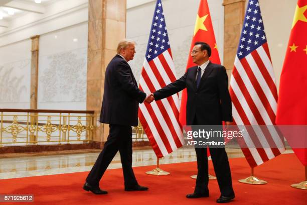 US President Donald Trump shakes hands with Chinese Premier Li Keqiang during a meeting at the Great Hall of the People in Beijing on November 9 2017...