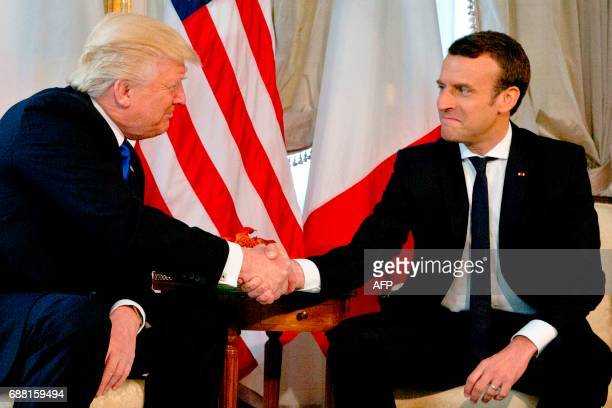 US President Donald Trump shakes hands with French President Emmanuel Macron ahead of a working lunch at the US ambassador's residence on the...