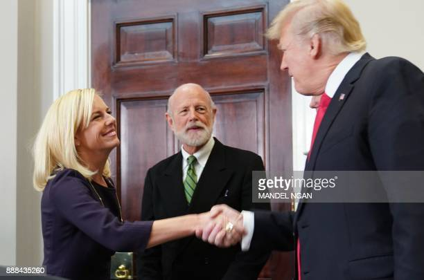 US President Donald Trump shakes hands with Homeland Security Secretary Kirstjen Nielsen after she took the oath of office in the Roosevelt Room of...