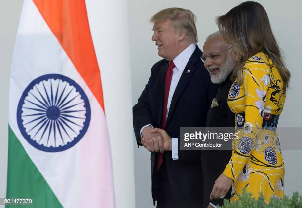 US President Donald Trump shakes hands with Indian Prime Minister Narendra Modi as he and First Lady Melania Trump walk with him along the West Wing...