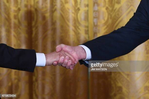 US President Donald Trump shakes hands with Italian Prime Minister Paolo Gentiloni during a joint press conference at the White House in Washington...