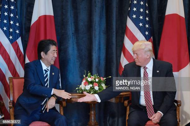 US President Donald Trump shakes hands with Japanese Prime Minister Shinzo Abe during a bilateral meeting at the Villa Diodoro on the sidelines of...