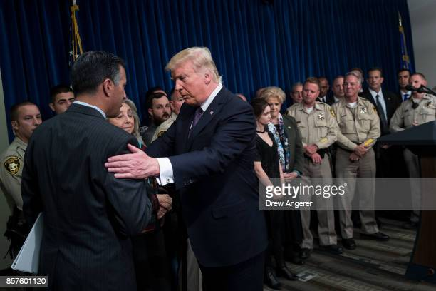 President Donald Trump shakes hands with Nevada Governor Brian Sandoval after speaking in a room full of police officers and family members at Las...