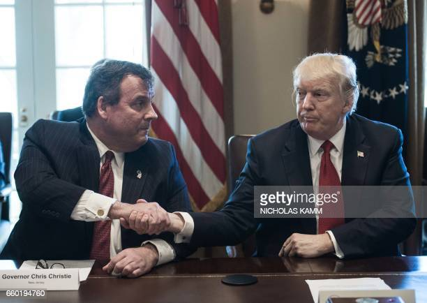 US President Donald Trump shakes hands with New Jersey Governor Chris Christie during a meeting about opioid and drug abuse in the Cabinet Room at...
