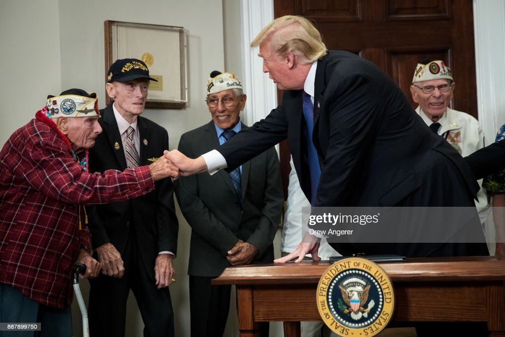 U.S. President Donald Trump shakes hands with Pearl Harbor survivor Larry Parry (L) before signing a proclamation for National Pearl Harbor Remembrance Day, in the Roosevelt Room of the White House, December 7, 2017 in Washington, DC. Thursday is the 76th anniversary of the attacks against the Hawaii naval base.