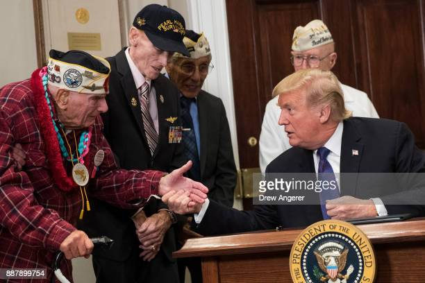 S President Donald Trump shakes hands with Pearl Harbor survivor Larry Parry after signing a proclamation for National Pearl Harbor Remembrance Day...
