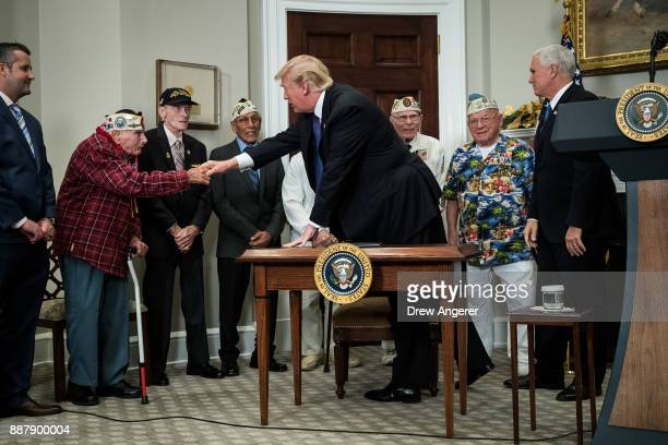 S President Donald Trump shakes hands with Pearl Harbor survivor Larry Parry before signing a proclamation for National Pearl Harbor Remembrance Day...