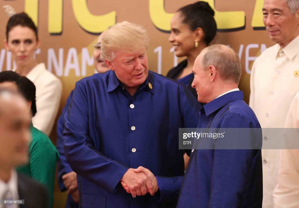 President Donald Trump (L) shakes hands with Russia's President Vladimir Putin (R) as they pose for a group photo ahead of the Asia-Pacific Economic Cooperation (APEC) Summit leaders gala dinner in the central Vietnamese city of Danang on November 10, 2017. World leaders and senior business figures are gathering in the Vietnamese city of Danang this week for the annual 21-member APEC summit. / AFP PHOTO / Vietnam News Agency / STR