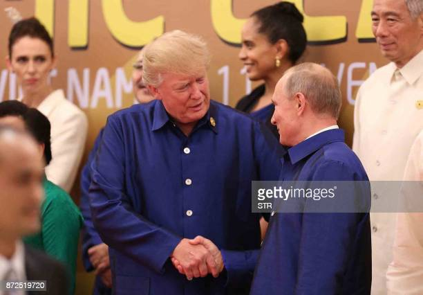 President Donald Trump shakes hands with Russia's President Vladimir Putin as they pose for a group photo ahead of the AsiaPacific Economic...